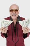 Ritratto dell'uomo senior allegro con le banconote degli Stati Uniti contro fondo grigio Fotografia Stock Libera da Diritti