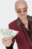 Ritratto dell'uomo senior che mostra le banconote degli Stati Uniti contro il fondo grigio Immagine Stock
