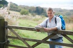 Ritratto dell'uomo senior con la mappa sull'aumento in campagna che riposa B fotografia stock
