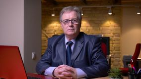 Ritratto dell'uomo senior in costume convenzionale che si siede davanti al computer portatile e che guarda seriamente nella macch video d archivio