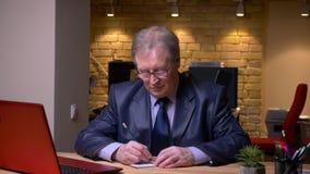 Ritratto dell'uomo senior nel funzionamento convenzionale del costume con il computer portatile e delle note di scrittura in tacc archivi video