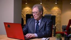 Ritratto dell'uomo senior nel funzionamento convenzionale del costume con il computer portatile in ufficio video d archivio