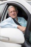Ritratto dell'uomo senior sorridente che conduce automobile Fotografie Stock