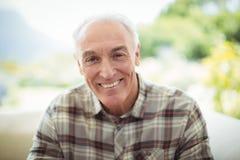 Ritratto dell'uomo senior sorridente che si siede sul sofà in salone fotografia stock