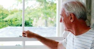 Ritratto dell'uomo senior sorridente che sta accanto alla finestra stock footage