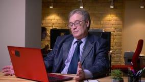 Ritratto dell'uomo senior in vetri nel funzionamento convenzionale del costume con il computer portatile che è attento in ufficio stock footage