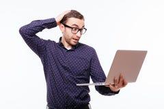 Ritratto dell'uomo serio con il computer portatile Uomo in vetri colpiti esaminando il computer portatile isolato su fondo bianco Fotografia Stock Libera da Diritti