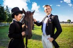 Ritratto dell'uomo sicuro che sta con il cavallo e la donna sul campo Immagini Stock Libere da Diritti