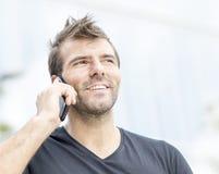 Ritratto dell'uomo sorridente che parla sul telefono. Fotografia Stock