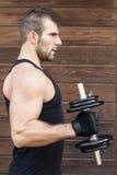 Ritratto dell'uomo sportivo che esercita le teste di legno. fotografie stock libere da diritti