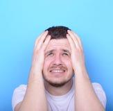 Ritratto dell'uomo triste che cerca contro il fondo blu Fotografie Stock