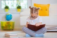 Ritratto della bambina abile che si siede con il libro sul pavimento Fotografia Stock