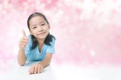 Ritratto della bambina asiatica di sorriso che mostra pollice su con la copia s Fotografia Stock