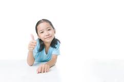 Ritratto della bambina asiatica di sorriso che mostra pollice su con la copia s Fotografie Stock