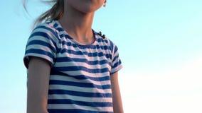 Ritratto della bambina attraente in camicia a strisce sul fondo del cielo con il tramonto di sviluppo dei capelli video d archivio