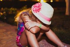 Ritratto della bambina bionda triste che si siede sulla terra Fotografie Stock Libere da Diritti