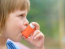 Ritratto della bambina che per mezzo dell'inalatore di asma all'aperto immagini stock