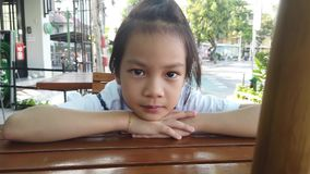 Ritratto della bambina che si siede nella disposizione dei posti a sedere all'aperto del caffè archivi video