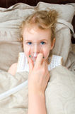 Ritratto della bambina che si trova a letto con l'inalatore Immagine Stock