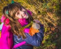 Ritratto della bambina con una condizione delle foglie di autunno in natura fotografia stock