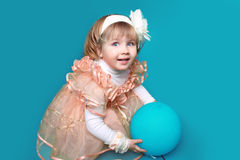 Ritratto della bambina divertente che gioca con il pallone sopra il BAC blu Immagini Stock