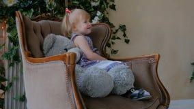 Ritratto della bambina divertente con la bambola dell'orso a casa archivi video