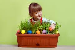 Bambina graziosa che cerca le uova di Pasqua Immagine Stock
