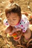 Ritratto della bambina nel pomeriggio che si siede sulla terra Fotografia Stock