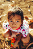 Ritratto della bambina nel pomeriggio che si siede sulla terra Immagini Stock Libere da Diritti