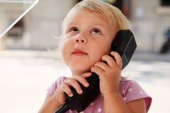Ritratto della bambina sorpresa che parla sul telefono della via Fotografie Stock Libere da Diritti