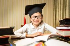 Ritratto della bambina sorridente in cappello di graduazione che si siede alla linguetta Fotografia Stock