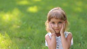 Ritratto della bambina sorridente sveglia in parco sul fondo dell'erba verde archivi video