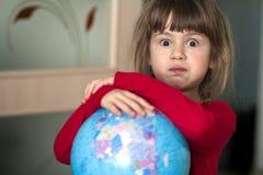 Ritratto della bambina sveglia che abbraccia il globo della terra L'istruzione e conserva il concetto della terra Bambino grazios Immagine Stock