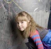 Ritratto della bambina sveglia con il libro e della mela verde vicino alla lavagna Fotografia Stock