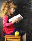 Ritratto della bambina sveglia con il libro e della mela verde vicino a blac Immagine Stock