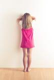 Ritratto della bambina triste che sta parete vicina Fotografie Stock Libere da Diritti