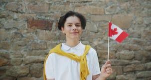 Ritratto della bandiera canadese della tenuta dell'adolescente del Canada che sorride che esamina macchina fotografica video d archivio