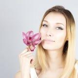 Ritratto della bionda sorridente con il fiore rosa Fronte di bellezza della donna Fotografia Stock