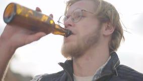 Ritratto della birra bevente dell'uomo biondo all'aperto che distoglie lo sguardo Uomo barbuto in vetri che gode della sua bevand video d archivio