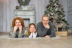 Ritratto della bugia felice della famiglia su un tappeto vicino all'albero di Natale Immagini Stock Libere da Diritti