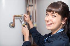 Ritratto della caldaia femminile del riscaldamento di Working On Central dell'idraulico Immagini Stock