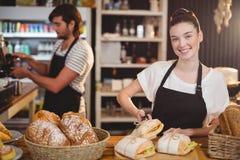 Ritratto della cameriera di bar che sta al contatore con i panini ed il panino Fotografie Stock Libere da Diritti