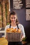 Ritratto della cameriera di bar che tiene un canestro con i viennoiseries Immagine Stock
