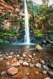 Ritratto della cascata e del cliffside soli dell'insenatura con uno stagno blu Fotografie Stock Libere da Diritti