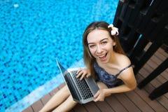 Ritratto della cima della macchina fotografica di sguardo femminile felice con il computer portatile sopra Immagine Stock