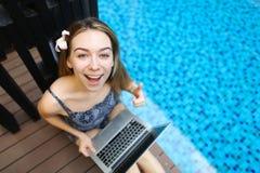 Ritratto della cima della macchina fotografica di sguardo femminile felice con il computer portatile sopra Immagine Stock Libera da Diritti