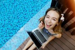 Ritratto della cima della macchina fotografica di sguardo femminile felice con il computer portatile su fondo della piscina Fotografie Stock