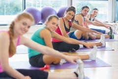 Ritratto della classe e dell'istruttore di forma fisica che allungano le gambe Immagini Stock