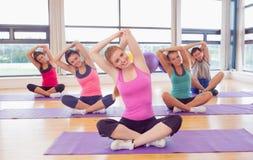 Ritratto della classe e dell'istruttore di forma fisica che allungano le mani sulle stuoie di yoga Fotografie Stock