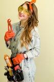 Ritratto della commessa attraente con capelli biondi lunghi e vetri gialli nel deposito di miglioramento domestico con le pinze Fotografie Stock Libere da Diritti